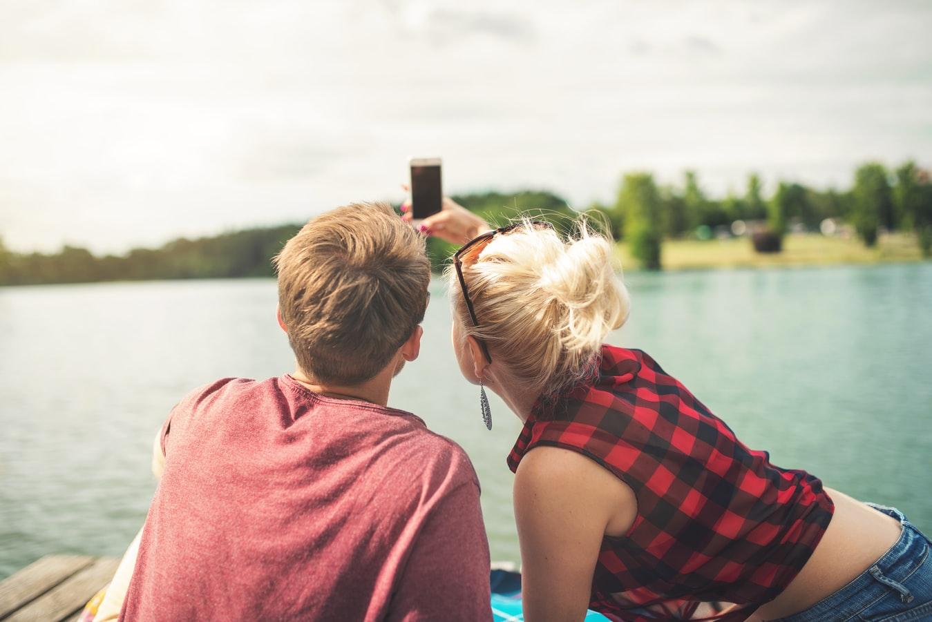 Un couple de jeunes gens prenant un selfie au bord d'un magnifique lac