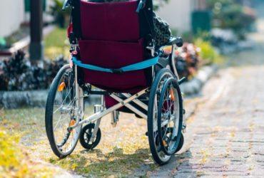 Une personne en fauteuil roulant dans une petite rue.