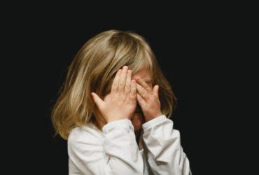 Une enfant se cachant le visage avec la main.