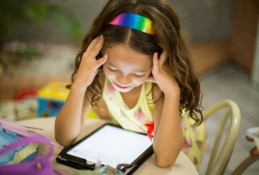 Une petite fille concentrée sur sa tablette.